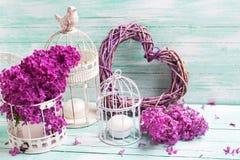 Fiori, lanterne e cuore lilla viola su turchese di legno Fotografia Stock