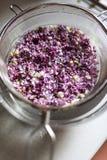 Fiori lilla di lavaggio in un setaccio fotografie stock