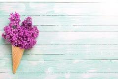 Fiori lilla freschi nel cono della cialda sul backgro di legno del turchese Fotografia Stock