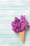 Fiori lilla freschi nel cono della cialda sul backgro di legno del turchese Fotografia Stock Libera da Diritti