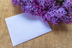 Fiori lilla in un vaso lilla ed in una busta con un posto per un'iscrizione cartolina immagini stock