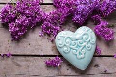 Fiori lilla viola e cuore decorativo del turchese sul wo invecchiato Fotografia Stock