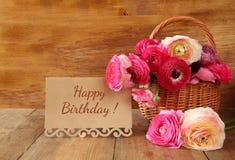 Fiori nel canestro accanto alla carta con la frase: buon compleanno Fotografie Stock