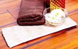 Fiori nell'acqua, nell'asciugamano e nella lozione Fotografia Stock Libera da Diritti