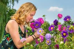 Fiori odoranti di estate della giovane donna in giardino immagini stock