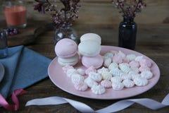 Fiori pastelli della caramella gommosa e molle su un piatto rosa su un fondo di legno rustico con i fiori della molla fotografia stock libera da diritti