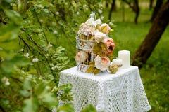 Fiori rosa, candele sul panno tricottato La decorazione sulla tavola nel parco Immagine Stock
