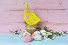 Fiori rosa delle uova di Pasqua, del pollo e di ciliegia su un fondo di legno blu Fotografia Stock Libera da Diritti