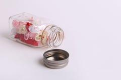 Fiori rosa, rossi, bianchi e crema svegli in un barattolo di vetro su un fondo bianco Immagini Stock