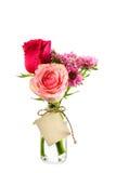 Fiori rossi e rosa in chiara bottiglia con l'etichetta sul backgro bianco Immagine Stock
