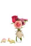Fiori rossi e rosa in chiara bottiglia con l'etichetta sul backgro bianco Immagine Stock Libera da Diritti
