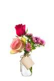 Fiori rossi e rosa in chiara bottiglia con l'etichetta sul backgro bianco Immagini Stock Libere da Diritti