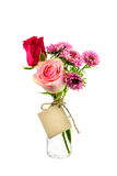 Fiori rossi e rosa in chiara bottiglia con l'etichetta sul backgro bianco Fotografia Stock