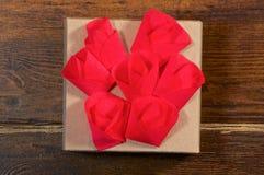 Fiori rossi sopra il primo piano del contenitore di regalo Immagine Stock