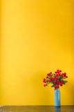Fiori rossi in vaso su fondo giallo Immagini Stock