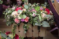 Fiori in scatola di legno con i chiodi di garofano, il alstromeria ed i verdi Immagini Stock