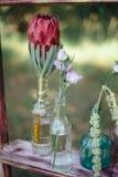 Fiori selvaggi nelle nozze delle bottiglie di vetro Fotografia Stock