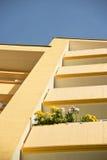Fiori su un balcone di una costruzione gialla Fotografia Stock