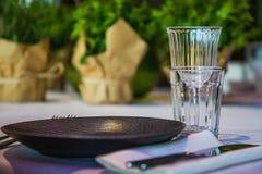 Fiori su una tavola di banchetto con i piatti vuoti Immagini Stock