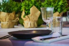 Fiori su una tavola di banchetto con i piatti vuoti Fotografia Stock