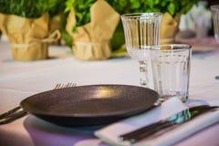 Fiori su una tavola di banchetto con i piatti vuoti Fotografia Stock Libera da Diritti