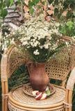 Fiori in un vaso su una sedia di vimini immagine stock libera da diritti