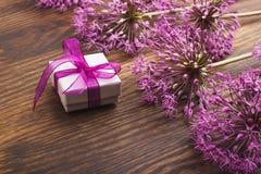 Fiori viola e una scatola sul bordo di legno Immagine Stock
