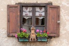 Fiorisca Arragement sulle finestre di una casa alpina Immagine Stock