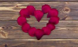 Fiorisca i petali che formano un anello di forma del cuore contro il fondo di legno marrone Fotografie Stock