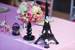 Fiorisca il mazzo con la torre Eiffel su una tavola di nozze Immagini Stock