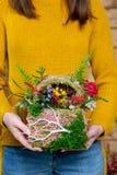 Fiorisca la composizione in mani del fiorista nella fase di completamento immagine stock libera da diritti