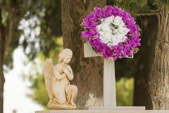 Fiorisca la ghirlanda e una statua su una tomba dopo un funerale immagini stock libere da diritti