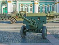 Fiorisce i garofani rossi nel barilotto della pistola dell'artiglieria Immagine Stock Libera da Diritti