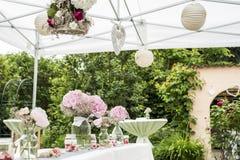 Fiorisce la messa a punto all'aperto della decorazione delle regolazioni per nozze con il fiore colorato rosa Immagini Stock