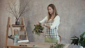 Fiorista affascinante che sistema i fiori nel negozio di fiorista stock footage