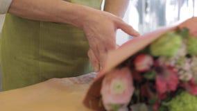 Fiorista che avvolge i fiori in carta al negozio di fiore stock footage