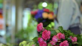 Fiorista che crea il mazzo del fiore al fondo vago delle rose video d archivio