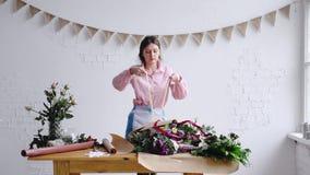 Fiorista che sistema mazzo nel negozio di fiore, legante nastro video d archivio