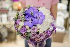 Fiorista che tiene la composizione tenera nel fiore nei toni blu, bianchi e porpora che consistono delle rose e di altri bei fior fotografia stock
