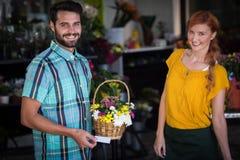 Fiorista e cliente femminili con il canestro del fiore ed il biglietto da visita Immagini Stock
