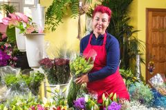 Fiorista felice della donna, prendente accordi e sorridente alla macchina fotografica Proprietario di negozio del fiore di piccol fotografie stock libere da diritti