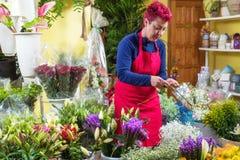 Fiorista felice della donna, prendente accordi e sorridente alla macchina fotografica Proprietario di negozio del fiore di piccol fotografie stock