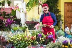 Fiorista felice della donna, prendente accordi e sorridente alla macchina fotografica Proprietario di negozio del fiore di piccol fotografia stock libera da diritti