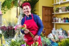 Fiorista felice della donna, prendente accordi e sorridente alla macchina fotografica Proprietario di negozio del fiore di piccol fotografia stock