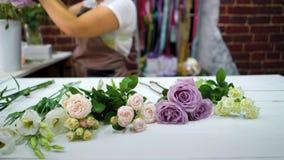 Fiorista femminile Defocused che mette i fiori sulla tavola di funzionamento che prepara alla disposizione di composizione video d archivio