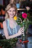 Fiorista femminile sorridente che sistema il mazzo del fiore in vaso al negozio di fiore Fotografia Stock