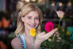 Fiorista femminile sorridente che sistema il mazzo del fiore in vaso al negozio di fiore Immagine Stock Libera da Diritti