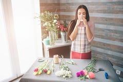 Fiorista femminile sul lavoro: bruna abbastanza giovane che rende a modo mazzo moderno dei fiori differenti Lavoro delle donne Immagine Stock