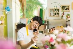 Fiorista maschio asiatico sorridente che rivolge allo smartphone ed a fare nota Fotografia Stock Libera da Diritti