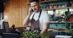 Fiorista maschio che parla sul telefono cellulare che tiene pianta verde che discute ordine video d archivio